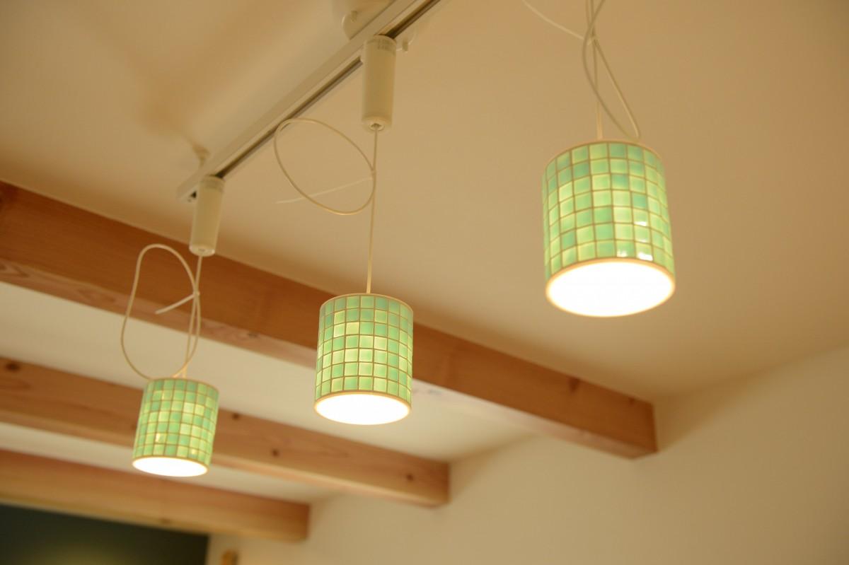 天井に木の温かみを感じる梁 タイルの素材が際立つ照明
