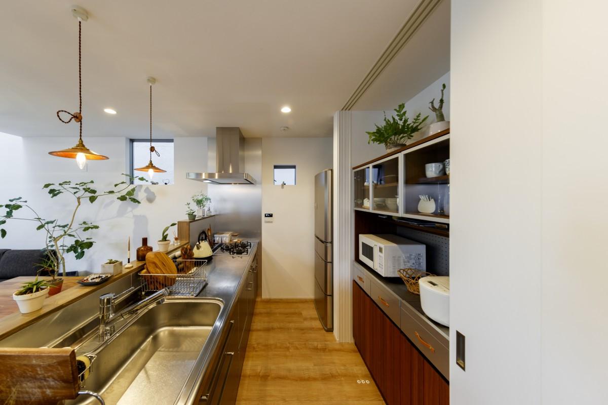 ステンレスのキッチンに木の壁や家具を配置 おしゃれなキッチンが完成
