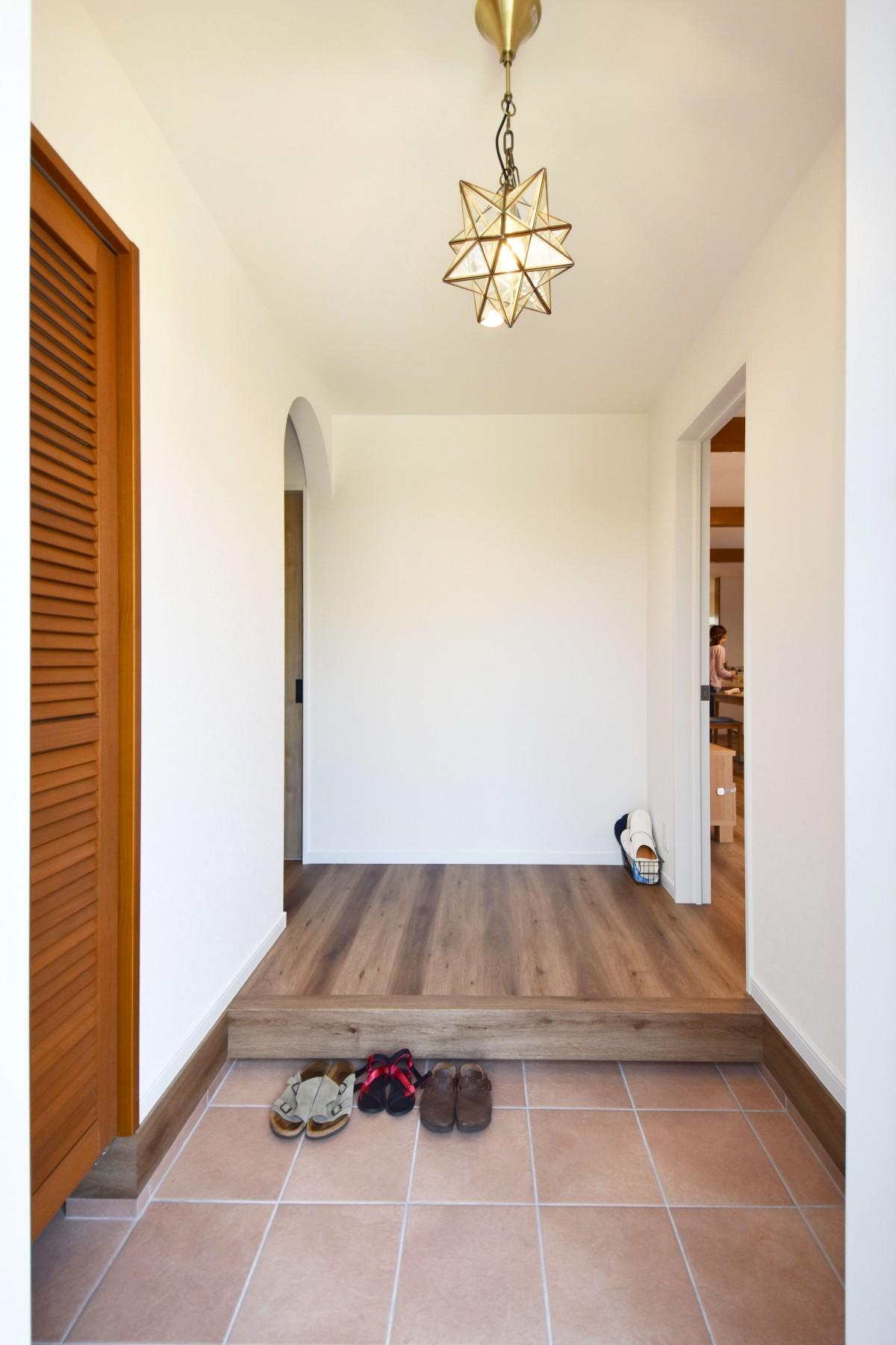 玄関にはアプローチから続くテラコッタ風のタイルを採用