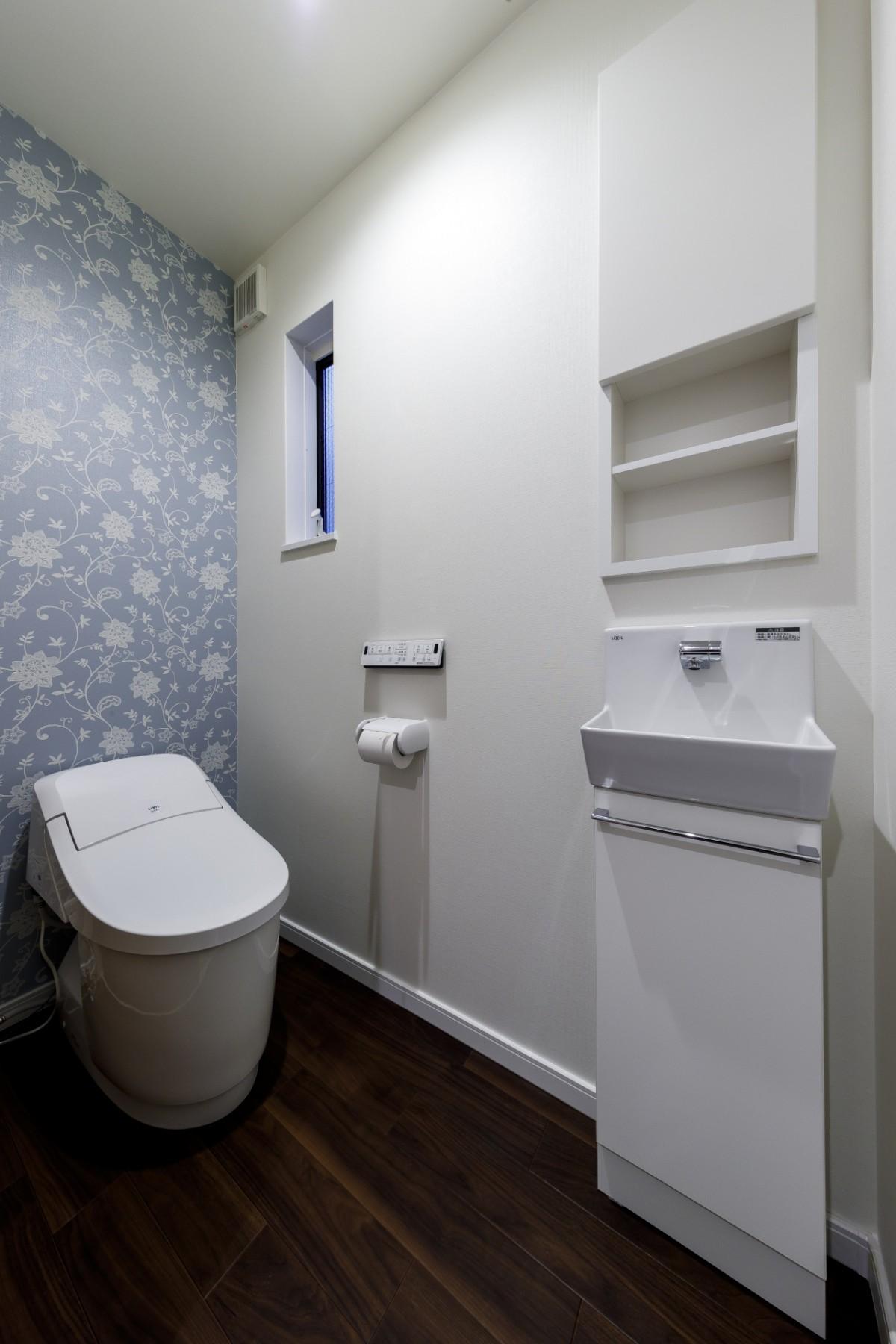 背面の壁紙アクセントにした清潔感のあるトイレ。