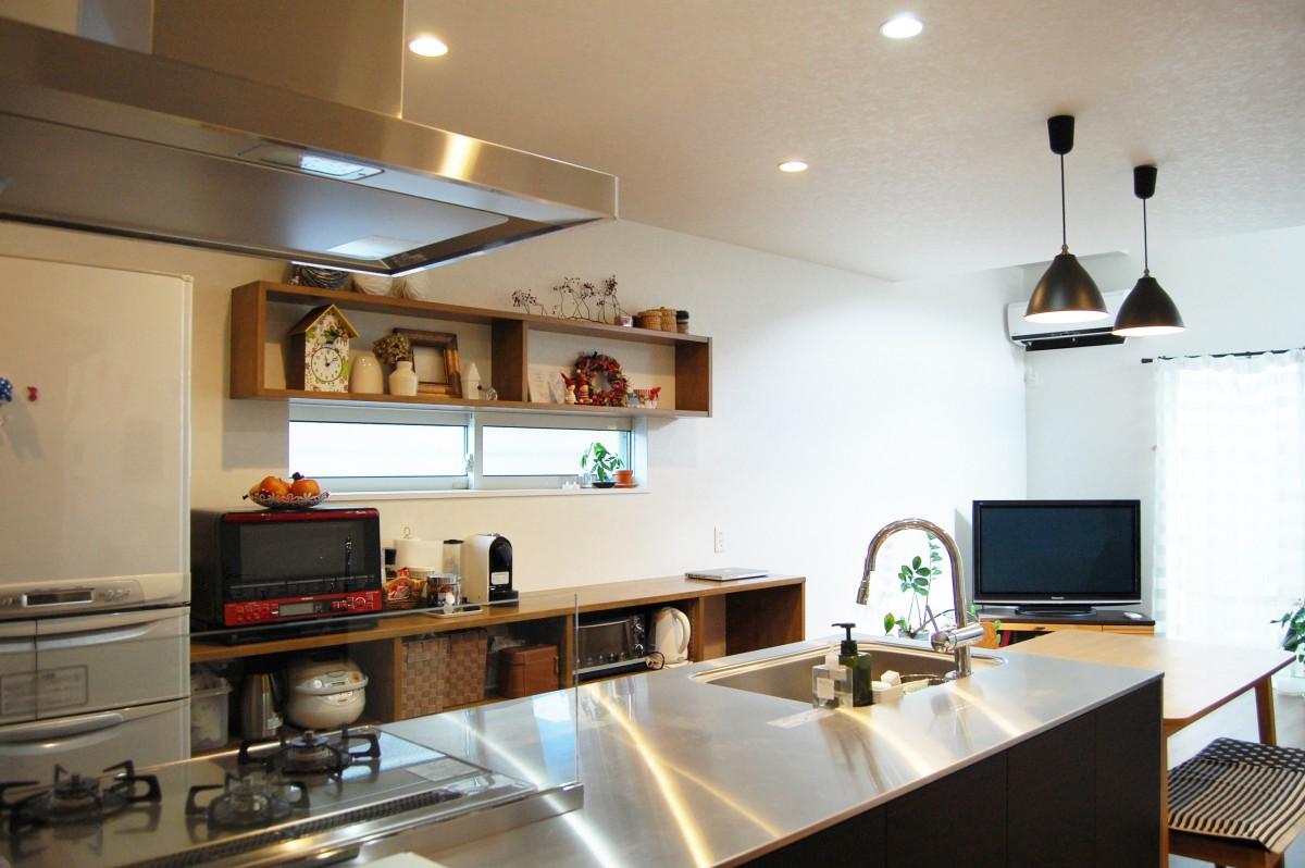 ステンレス製アイランドキッチンとハンモックのある2世帯で暮らす家