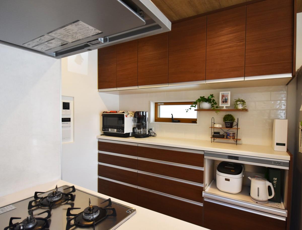 キッチンの背面には白色のタイルを装飾し緑や調味料も魅せる収納