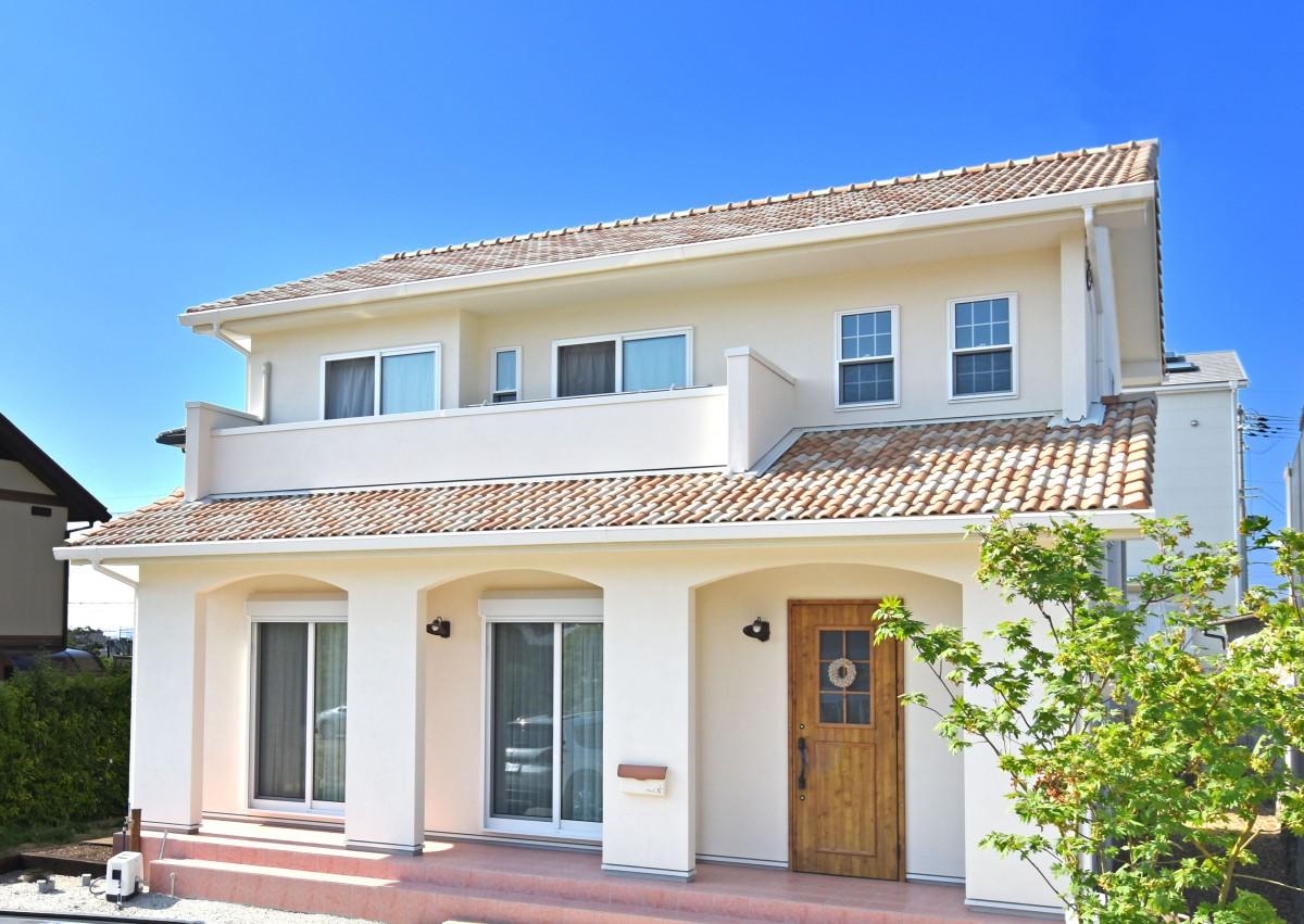 青い空に映える白い塗壁と瓦屋根がかわいい南欧風のお家