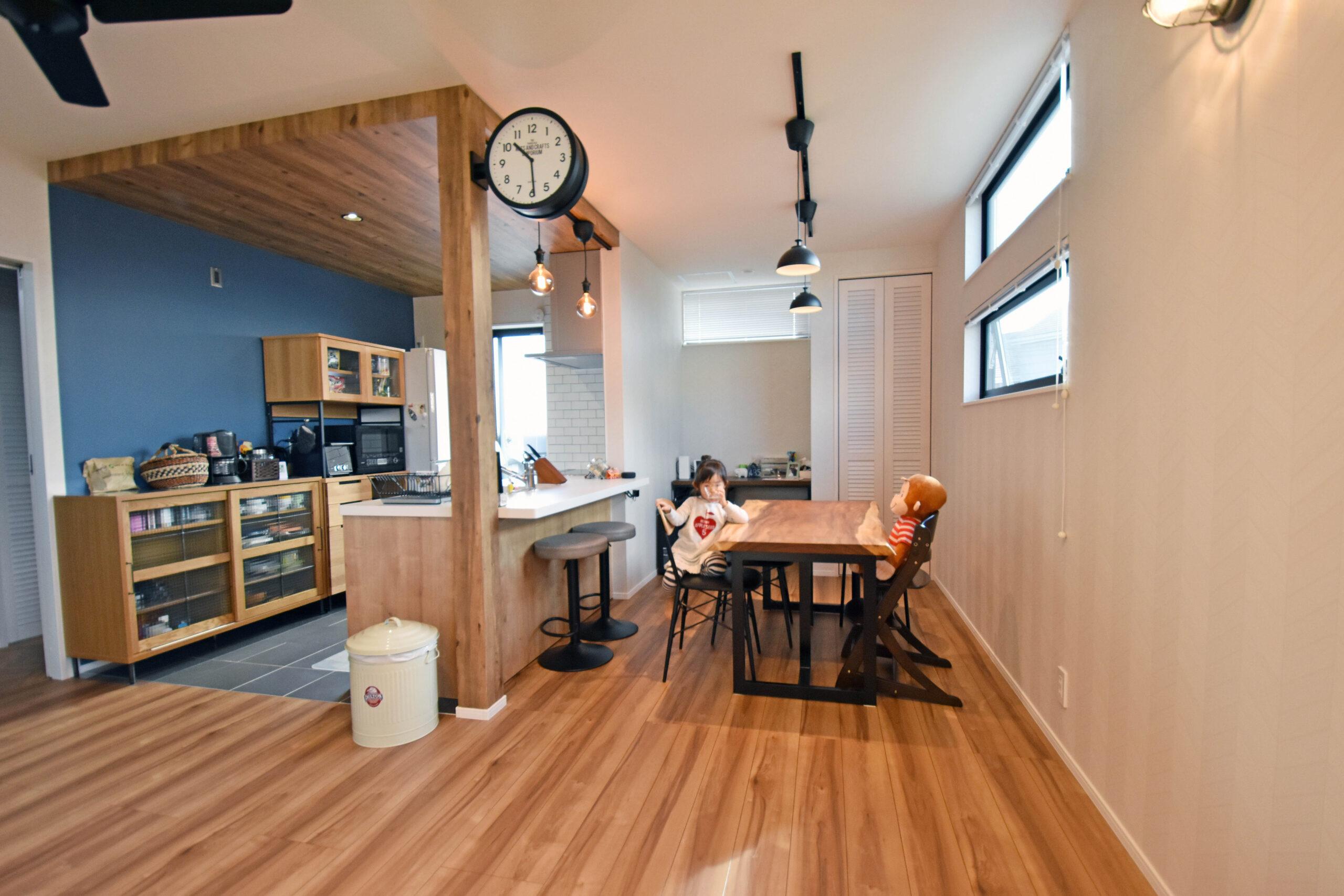 木目が特徴的なキッチン天井は、あえて低くし奥行きを演出。ブルーのアクセントクロスで毎日の料理が楽しくなりそう。
