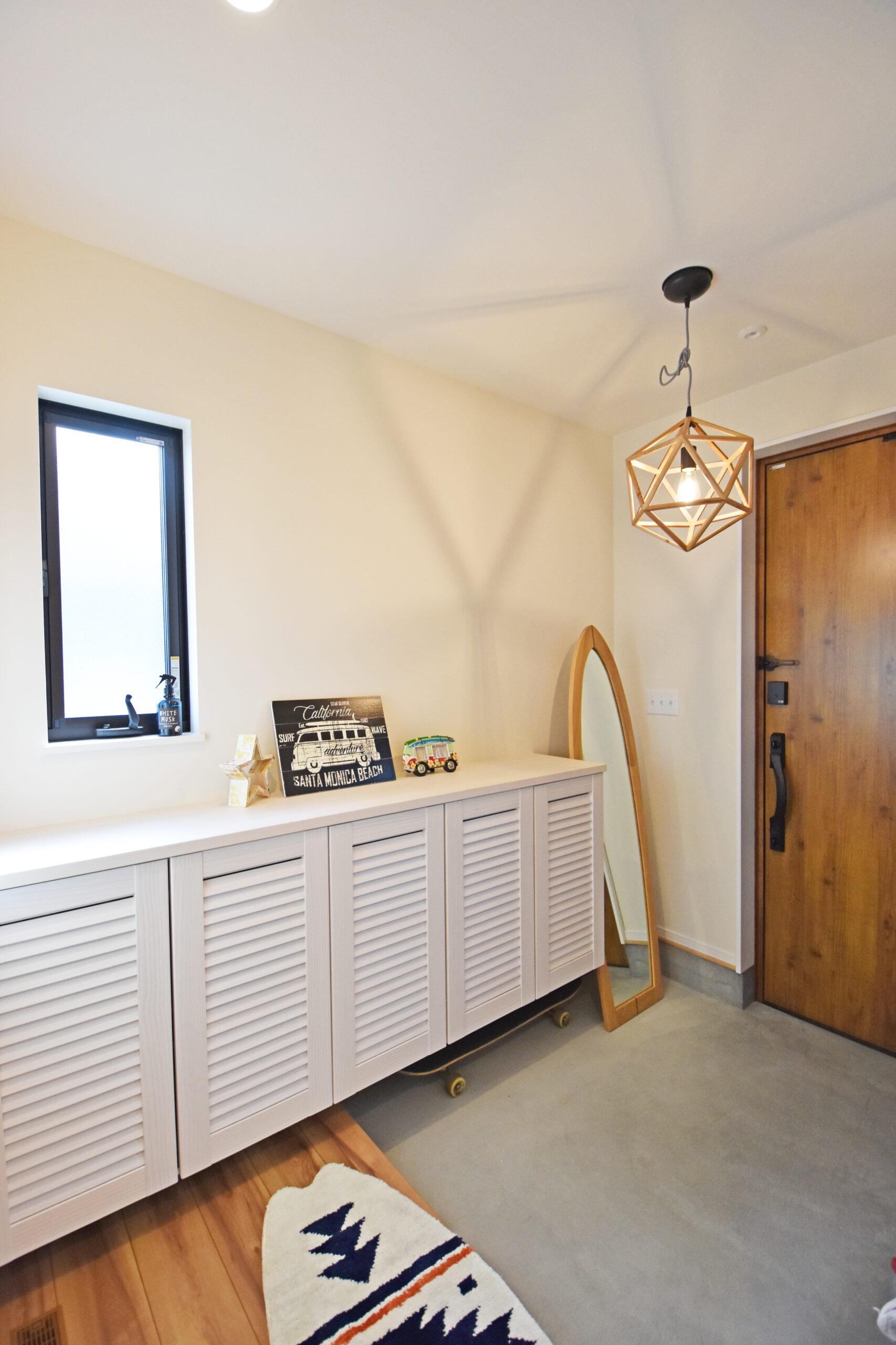 玄関スペースは白を基調とした。アクセントとなる照明の印影が美しい