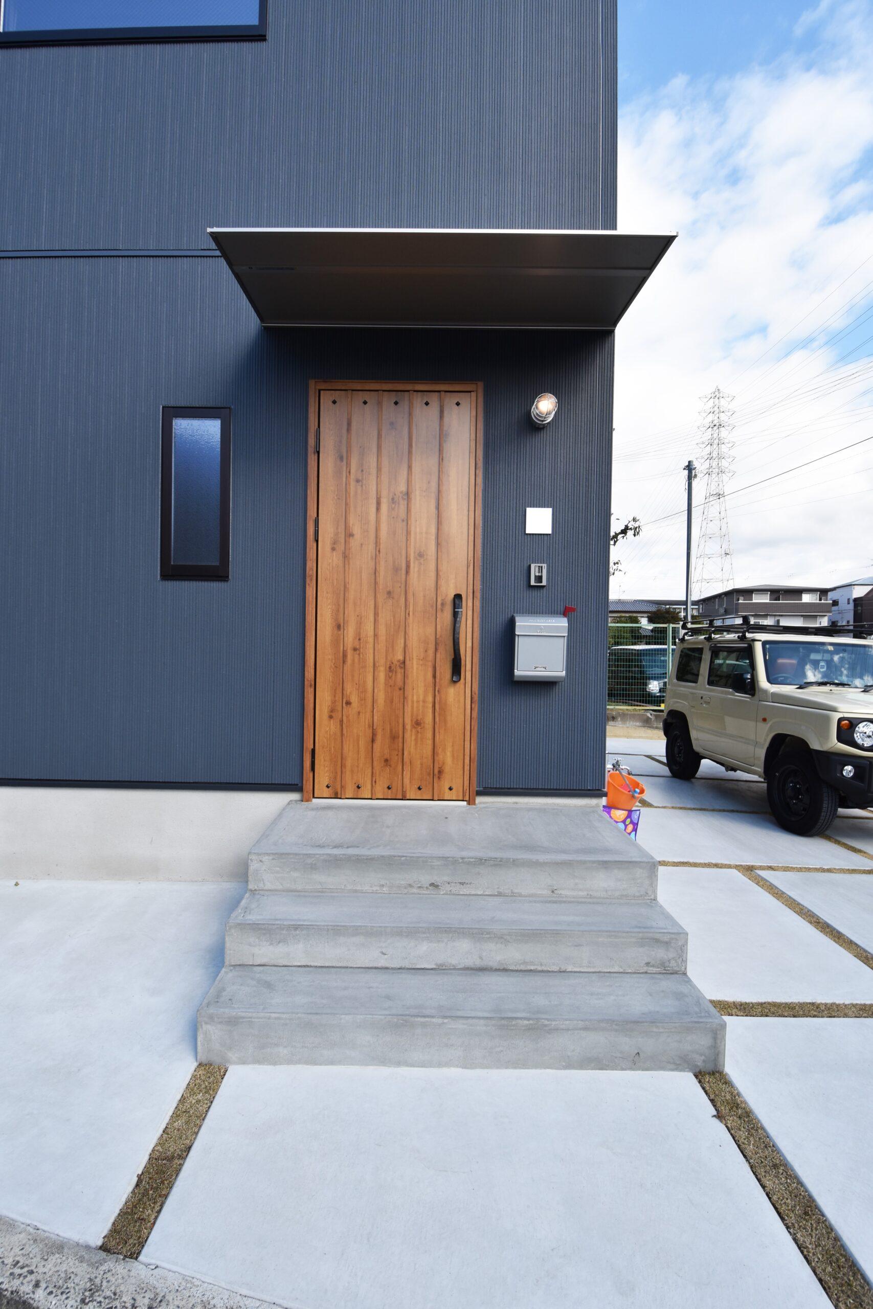 木目のドアとコンクリート、絶妙なブルーが相性抜群の外観。