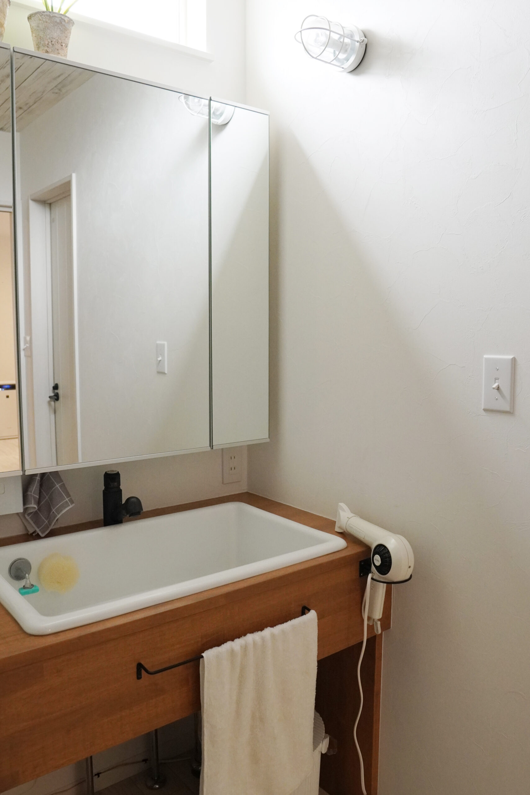 造作洗面。タオル掛けやドライヤーホルダーなどを、使いやすいようにカスタマイズした。
