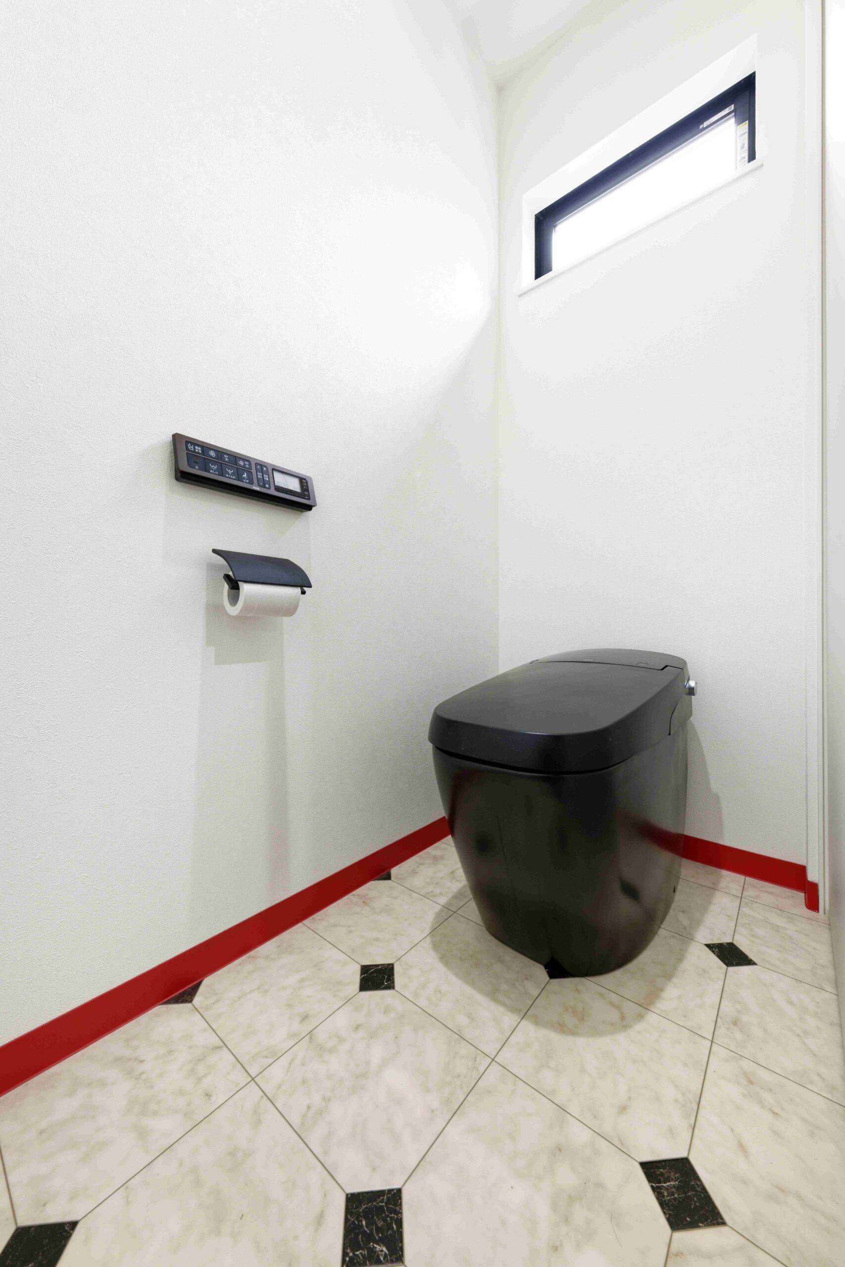 大理石風のと赤の巾木がアクセントの、黒いトイレ。