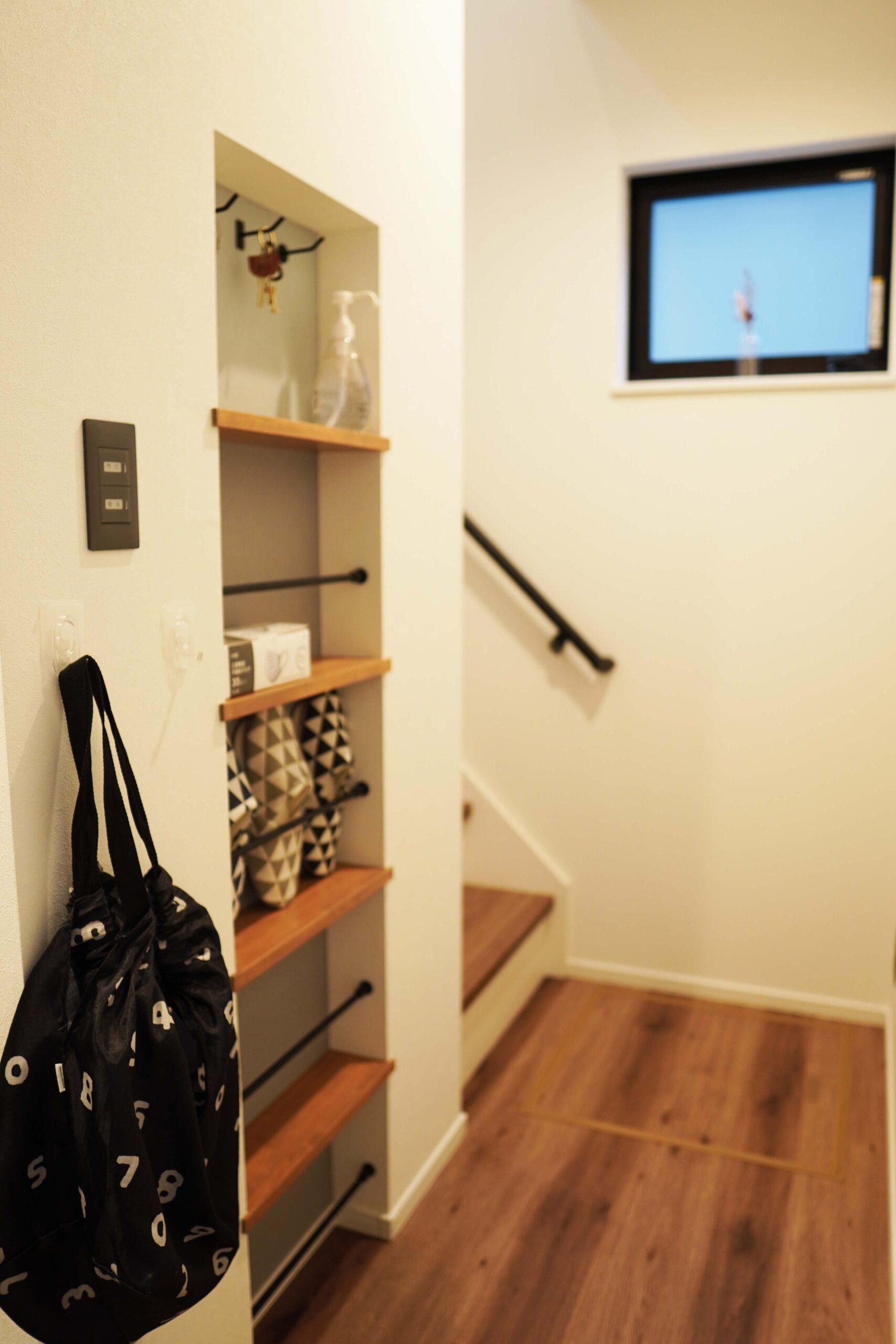 階段手前の壁をあえてくぼませることで、ちょっとした収納代わりに。マスクや鍵など外出時に必要な物をまとめて置いておくことができる。