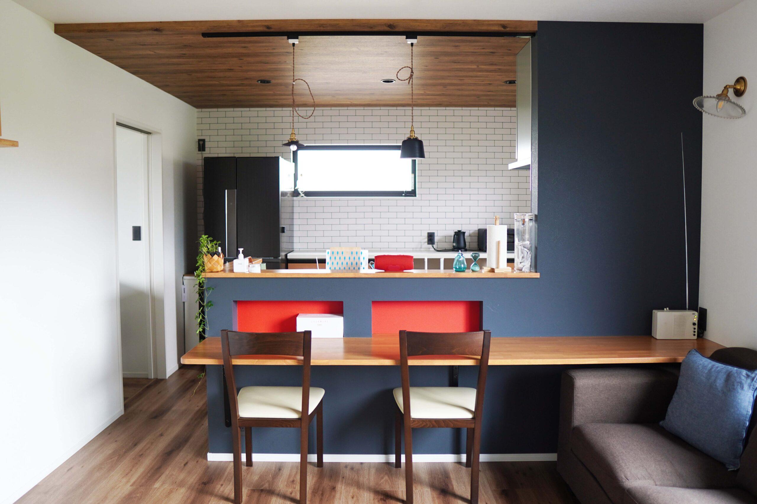 キッチン前には並んでかけられるカウンターを計画した。腰壁にニッチをつくることで、ちょっとした収納代わりに。アクセントクロスで視覚的にも楽しい空間になった。LDKはチャコールブラック×白を基調として、差し色に赤を使用。モダンな印象に仕上げた。