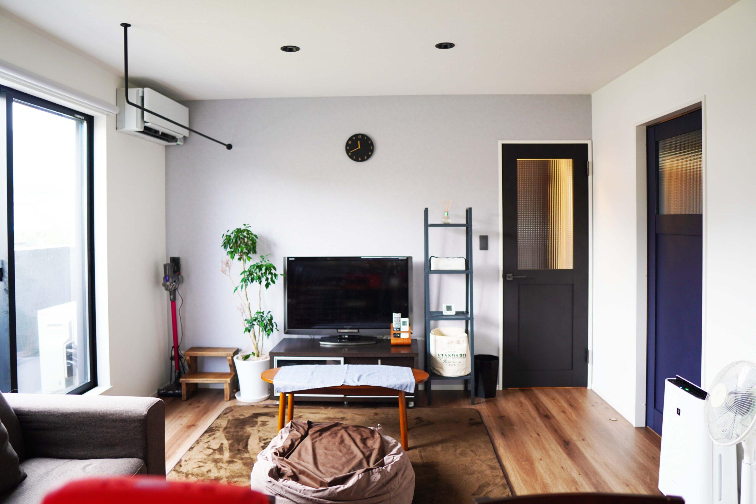白い壁に観葉植物の緑とチャコールブラックの扉の色合いがマッチしている。室内干しができるように、窓際にはアイアンのバーを設置した。