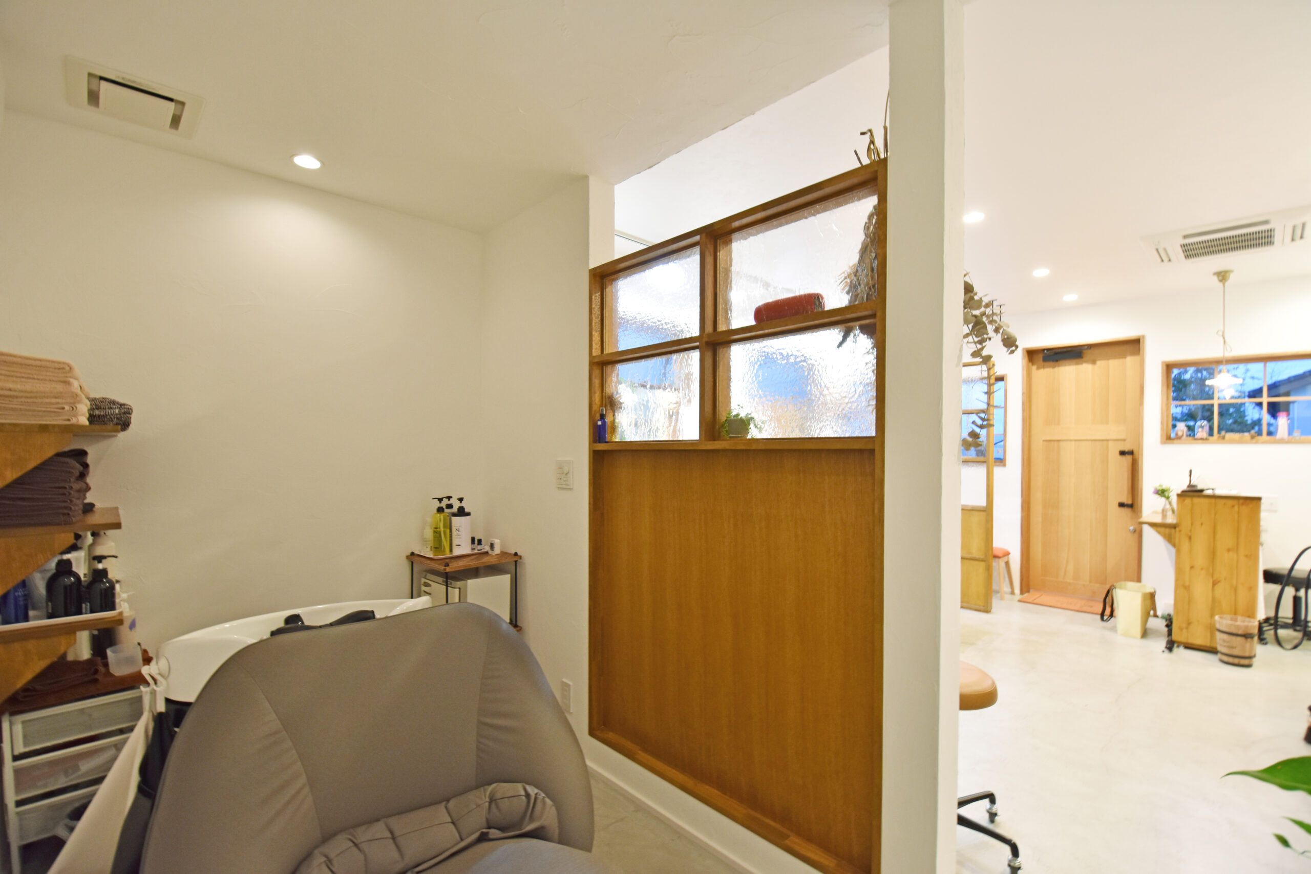 シャンプースペースとカットスペースの間には、間仕切りを設けて視線を遮りつつも、圧迫感のないように室内窓を採用。大工さん手作りの棚は高さや数を計算して作っているので、タオルやシャンプー類が収納しやすくなっている。