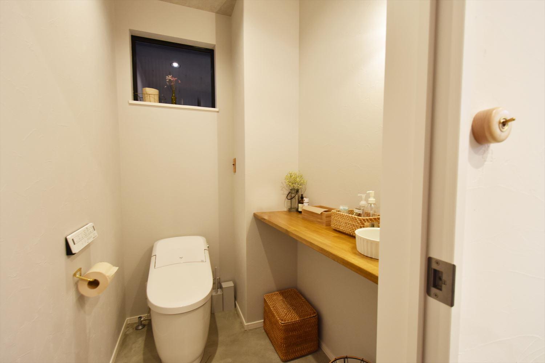 トイレの床にもモルタルを採用。掃除がしやすい機能性とデザイン性とを兼ね備えている。お客様用のペーパータオルや石鹸、アルコールが置けるように飾り棚は広めに設計。白い陶器のボウルが木のカウンターによく映えている。