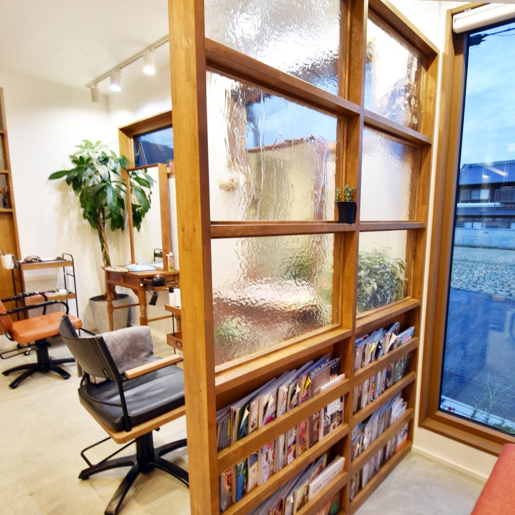 カットスペースと待合スペースの間に2種類のガラスを使った壁を設置。人の気配を感じながらも視線が合わない距離感を保てるようにしました。